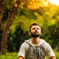 A,Bearded,Man,Is,Meditating,On,Green,Grass,In,The