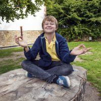 young boy smiles and has fun by meditating